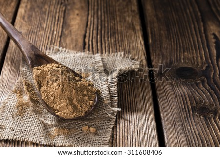 Heap of Guarana Powder (close-up shot) on wooden background - stock photo