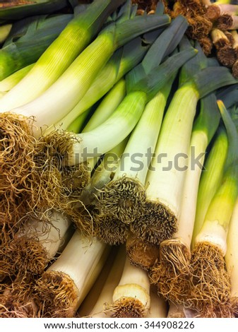 Heap of harvested leeks for sale at farmers market.