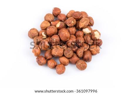Heap of hazelnuts isolated on white background, macro image - stock photo
