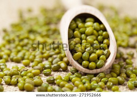 Heap of healthy organic green mung bean legume grain in wooden spoon on vintage textile background. Close up. - stock photo