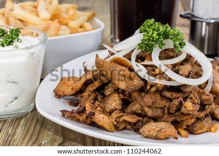 Heap of Kebab meat on a plate on wooden background - stock photo