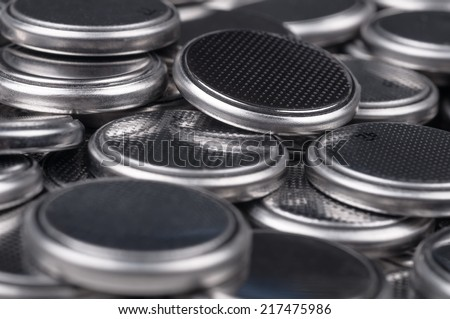 Heap of lithium button cell batteries. Closeup with shallow DOF. - stock photo