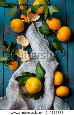 Heap of mandarins with green leaves on old wooden table - stock photo
