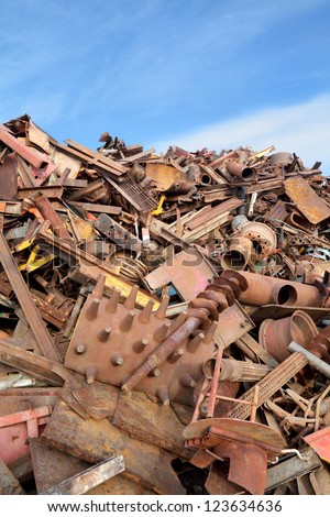 Heap of metal for recycling with blue sky - stock photo