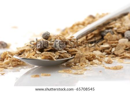 Heap of muesli and metallic spoon on white background. - stock photo