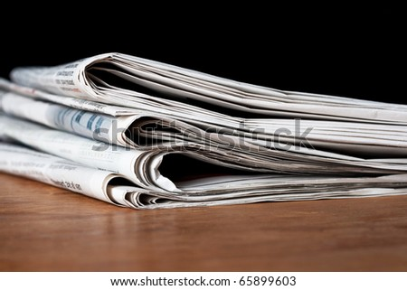 Heap of newspapers on a wooden table - stock photo