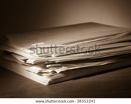 Heap of papers with a writing pad on top, toned
