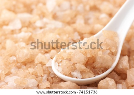 Heap of peach-colored bath salt with white ceramic spoon.