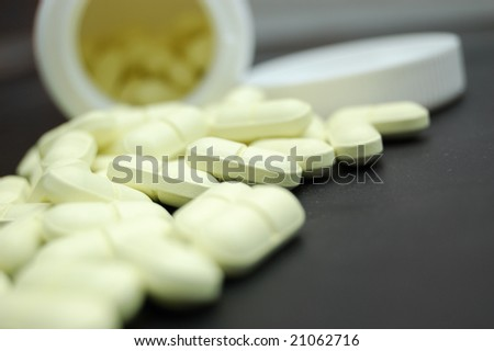 Heap of pills and container on black (shallow DOF). Selective focus. Closeup of tablets on black background. Pills close up. Drugs. Bright Medical background