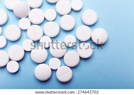 Heap of pills on color background