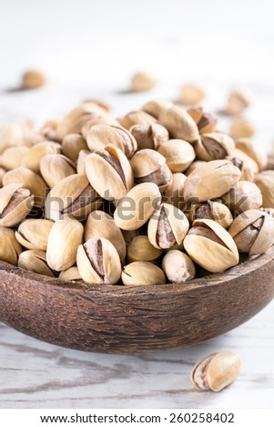 Heap of pistachios in the wooden bowl,selective focus and blank space  - stock photo