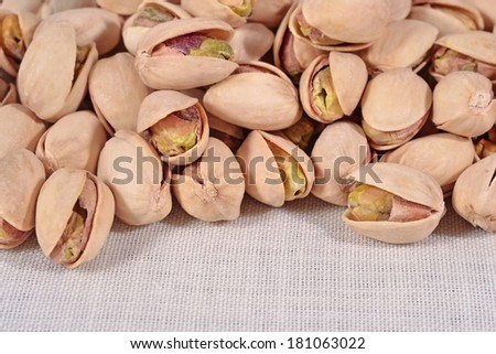 Heap of pistachios on a textile background - stock photo