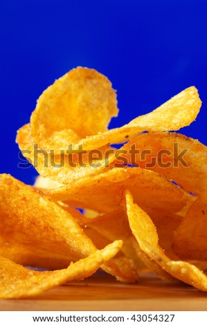 Heap of potato chips close-up on blue background.