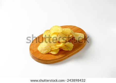 Heap of potato chips on a cutting board - stock photo