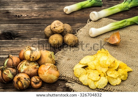 Heap of potato chips onion flavor on rustic jute and wooden background, shallow depth of field. - stock photo