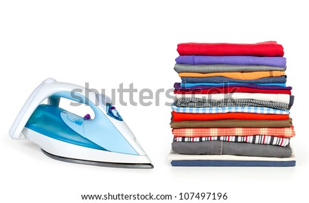 Heap of pure clothes with an iron isolated on white - stock photo