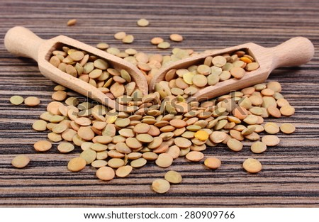 Heap of raw green lentil with wooden spoon lying on wooden background, concept for healthy nutrition and eating - stock photo