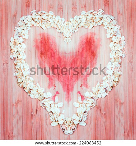 Heap of raw oatmeal flakes in a shape of heart on a wooden cutting board, fresh morning breakfast. Drama, tragedy, love, sadness concept - stock photo