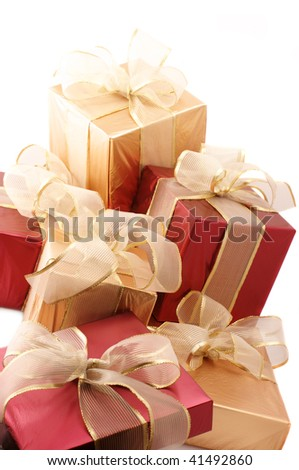 Heap of red and gold gifts with translucent gold bows on white background. - stock photo