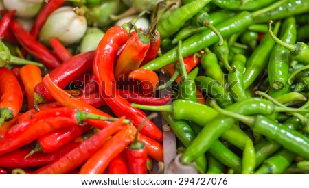 Heap of red and green Cayenne pepper (Capsicum annuum) is also called Guinea spice, cow-horn pepper, red hot chili pepper, aleva or bird pepper for retail sale in Thailand fresh food market - stock photo