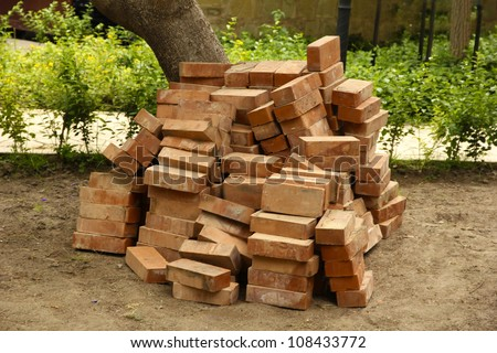 Heap of red bricks in yard - stock photo