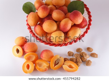 Heap of ripe apricots in a bowl and a few apricots with pits beside it on a white background. Cut apricots