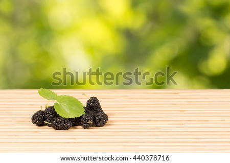 Heap of ripe black mulberries with green leaves on table on green leaves background with option to insert your product . Horizontal composition - stock photo