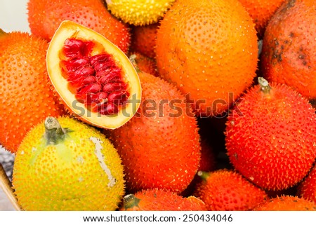 heap of ripe gac fruit in market - stock photo