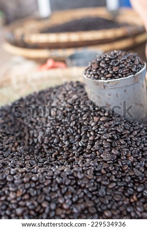 Heap of roasted black coffee beans on sell in indonesian market (Sulawesi). Selective focus, oblique view. - stock photo