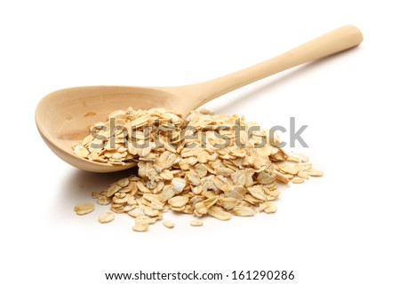 Heap of rolled oats with wooden spoon on white - stock photo