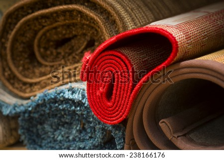 Heap of rolled up rugs in rug store - stock photo