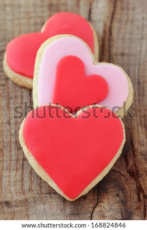 Heap of romantic heart shaped homemade Valentine cookies decorated with pink and red icing on rustic wooden background - stock photo