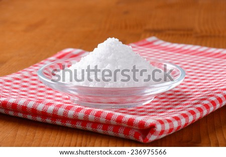 heap of salt in the glass bowl with patterned napkin - stock photo