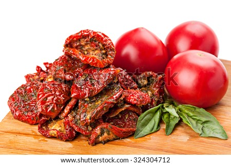 Heap of sun dried tomatoes with basil leaves and fresh ripe tomatoes, isolated on white background.Studio shot.