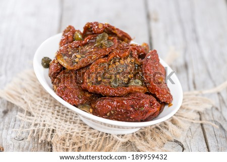 Heap of sun dried Tomatoes with fresh herbs on wooden background - stock photo