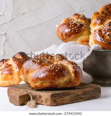 Heap of sweet round sabbath challah bread with white and black sesame seeds in vintage metal bowl and on cutting board over table with plastered wall at background. Square image with selective focus. - stock photo