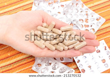 Heap of tablets in hand of woman and empty pills blisters in background - stock photo