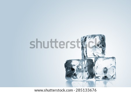 Heap of three ice cubes with reflection over blue background with copy space - stock photo