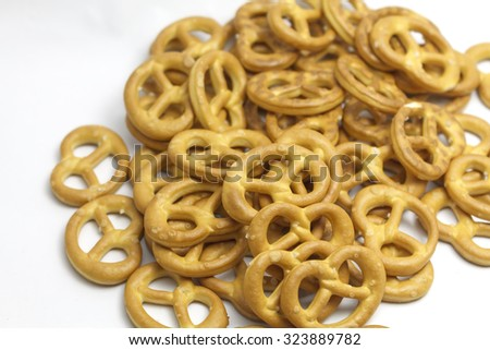 Heap of traditional salted mini pretzels for beer on isolated white background