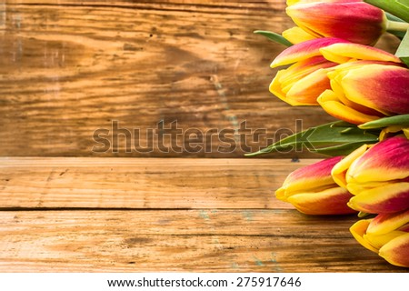 Heap of tulips as floral backgrounds. Tulips on a wooden planks background for mothers day, wedding invitation, greetings card and invitation cards - stock photo