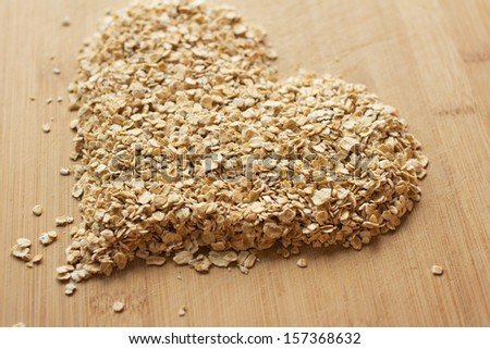 Heap of uncooked oats on a wooden chopping board arranged in the shape of a heart. - stock photo