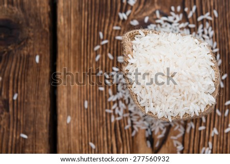 Heap of uncooked Rice (close-up shot) on wooden background - stock photo