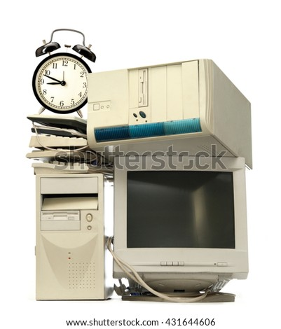 Heap of used computers and alarm clock - stock photo