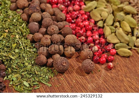 Heap of various kinds of dry spices on a wooden background