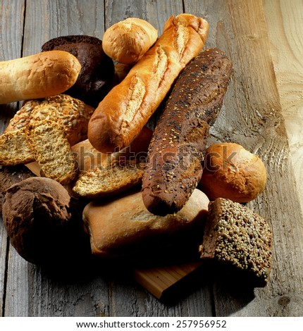 Heap of Various Various Buns, Baguette, Poppy Seed and Sesame Buns, Rye and Whole Wheat Bread isolated on Rustic Hardwood background - stock photo