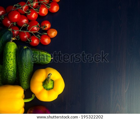 heap of vegetables is on the kitchen table. cherry tomatoes, red onion, celery, yellow pepper, cucumber - stock photo