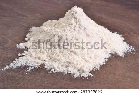 Heap of white flour on a wooden background - stock photo