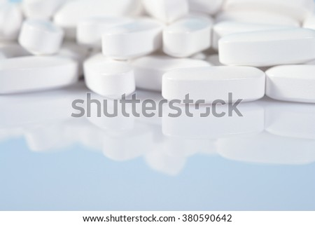 Heap of white pills close up on a blue background
