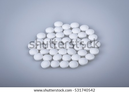 Heap of  white pills isolated on the light blue background. Selective focus.