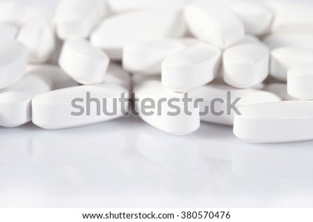 Heap of white pills on a white background